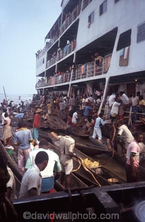 dugout;canoe;canoes;riverboat;stack;stacked;pile;pile_up;person;people;crowd;crowded;trade;trading;trader;traders;buy;buying;sell;selling;produce;river