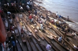 dugout;canoe;canoes;stack;stacked;pile;pile_up;person;people;crowd;crowded;trade;trading;trader;traders;buy;buying;sell;selling;produce;river