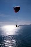 fly;flying;flies;soar;soaring;paraglide;paraglides;paragliders;paragliding;parapont;paraponts;paraponter;paraponters;paraponting;parasail;parasails;parasailer;parasailers;parasailing;cliff;bluff;jump;sea;ocean-sunlight;glare